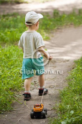 Маленький ребенок везет за собой машинку-ClipArtBank.ru-фотобанк,продажа лицензионных фотографий,изображений.Купить фотографию-М